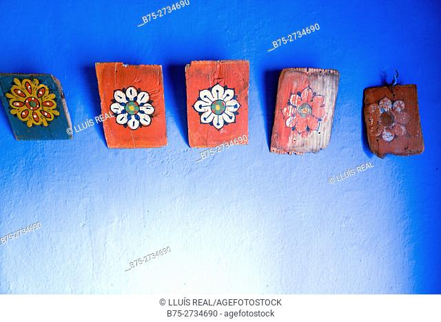 Paintings on wood hung on a blue wall. Chaouen, Morocco