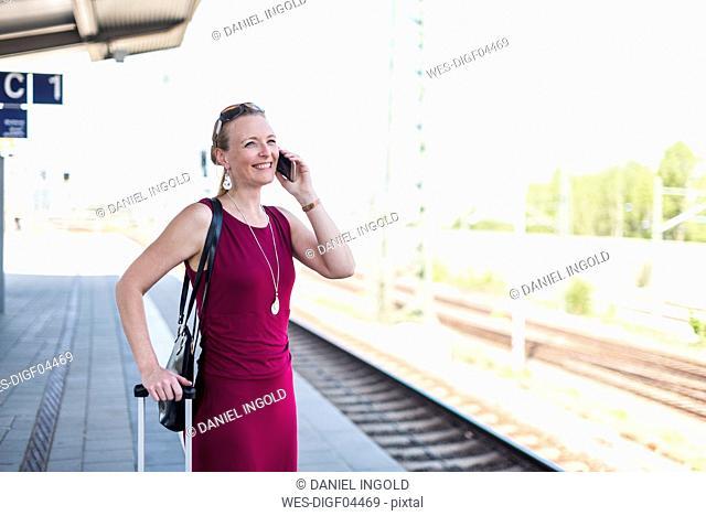 Smiling mature woman on the phone waiting at platform