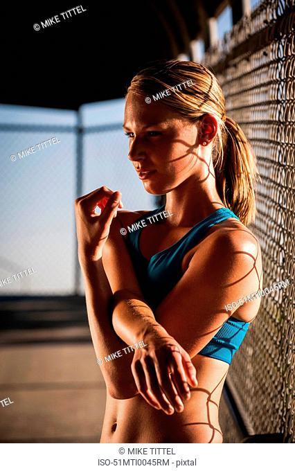 Woman stretching on urban footbridge