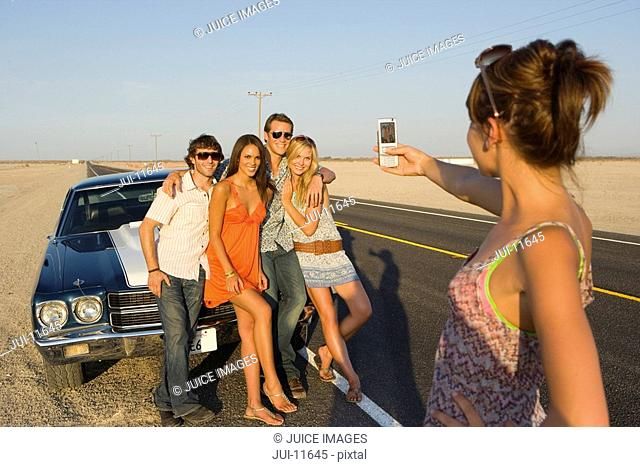 Young woman taking photograph of friends on bonnet of car on desert road, rear view