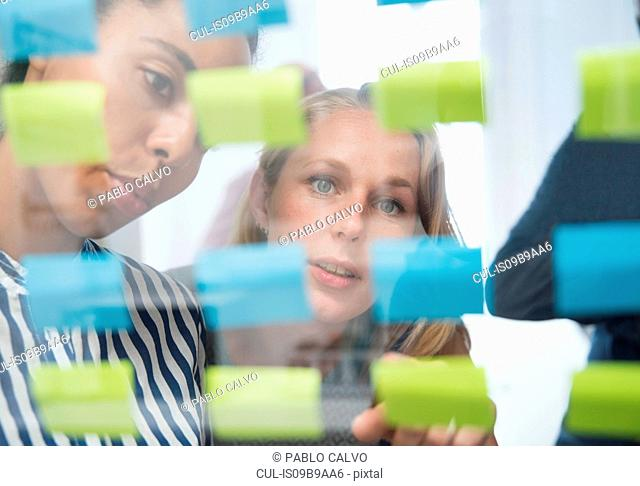 Two businesswomen behind glass wall pointing at adhesive notes