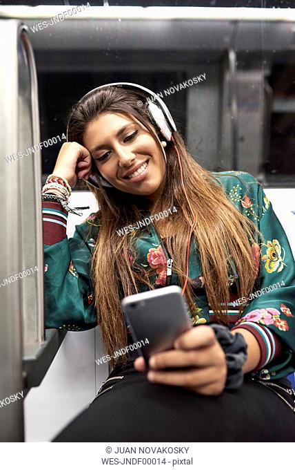 Portrait of smiling woman with headphones looking at cell phone in underground train