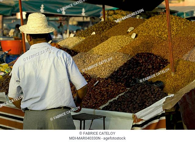 Jemaa El Fna place - Shopkeeper selling dried fruits on a stand
