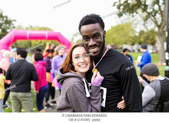 Portrait happy couple runners with medal at charity run in park