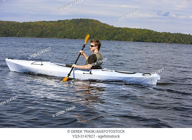 boy paddeling kayak in lake, North America, Canada, Ontario, Algonquin Provincial Park