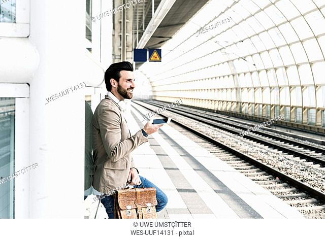 Smiling young man with cell phone at the station platform