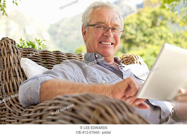 Portrait of smiling man using digital tablet on patio