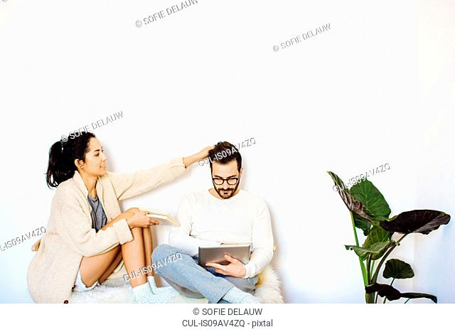 Young woman with hand in boyfriends hair whilst he uses digital tablet