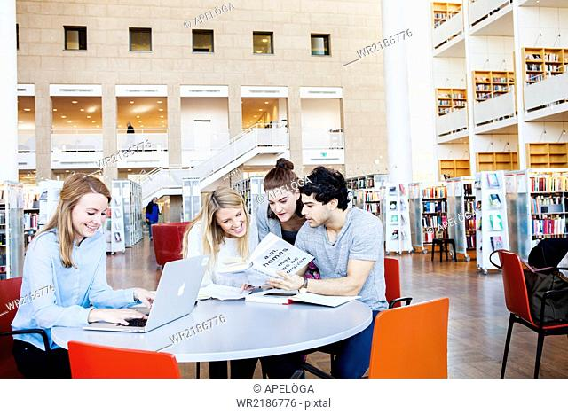 Happy friends reading novel together while woman using laptop in library