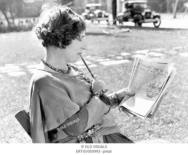 Woman with a pencil in her mouth reading the newspaper All persons depicted are not longer living and no estate exists Supplier warranties that there will be no...