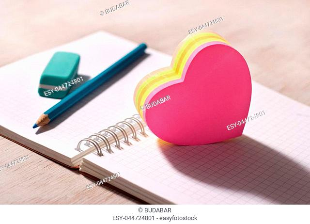 Heart shaped blank stickers on note book with pencil and eraser in background, on wooden desk. Place for your text