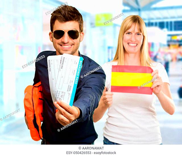 Man Holding Boarding Pass In Front Woman Holding Spain Flag, Indoor