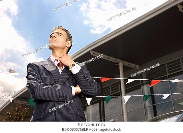 portrait of salesman at car dealer
