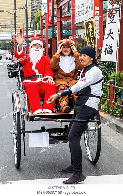Japan, Hoshu, Tokyo, Asakusa, Couple Dressed as Father Christmas and Reindeer in Rickshaw