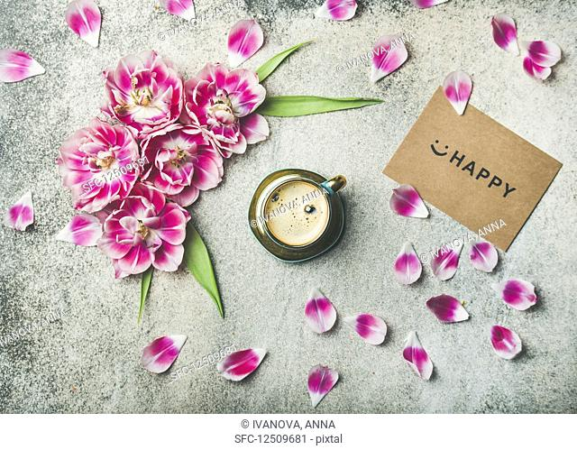 Cup of coffee surrounded with pink tulip flowers, petals and sign happy on paper