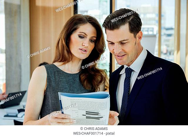 Businessman and woman discussing booklet in office