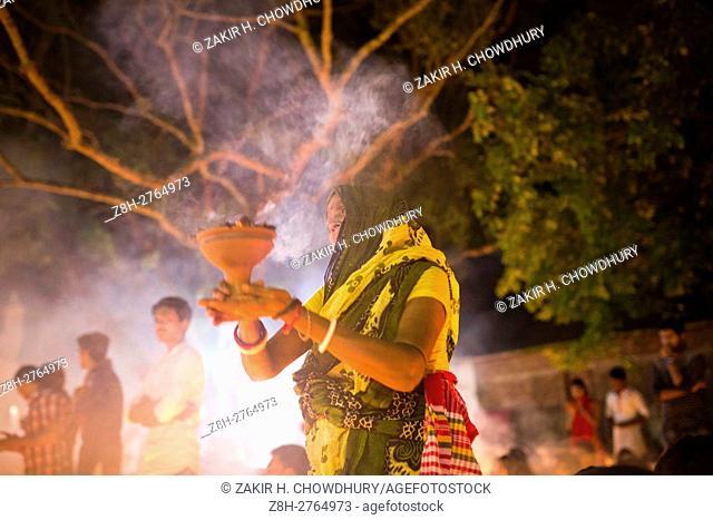 DHAKA, BANGLADESH - NOVEMBER 08 : Thousands of Hindu devotees sit with Prodip and pray to God in front of Shri Shri Lokanath Brahmachari Ashram temple during...