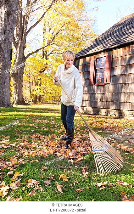 USA, New Jersey, Woman raking leaves in front of house
