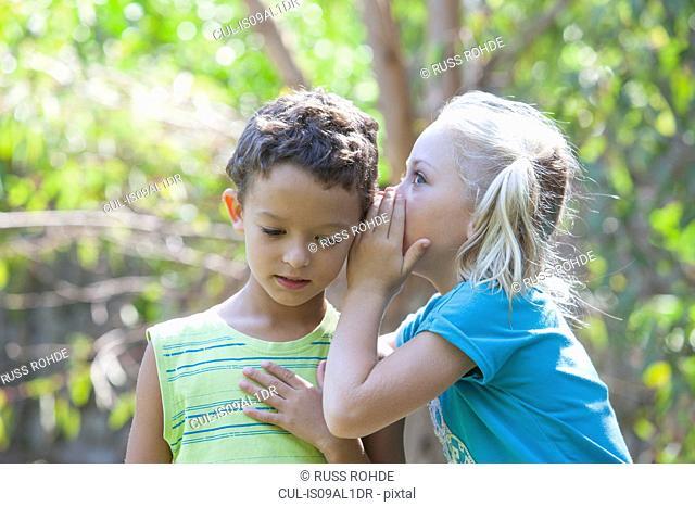 Girl whispering to boy in garden