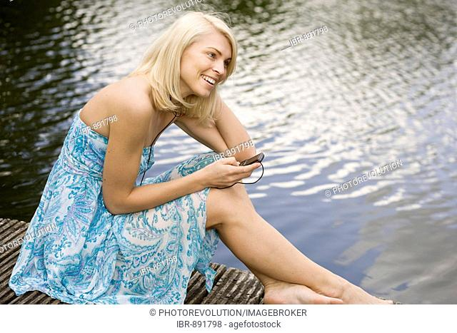Young blonde woman wearing a dress while sitting on a wharf at a lake and listening to music