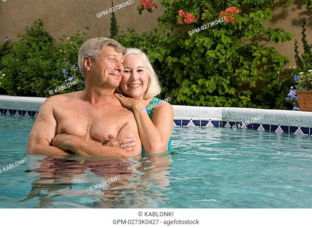 Mature couple standing close together affectionately in swimming pool