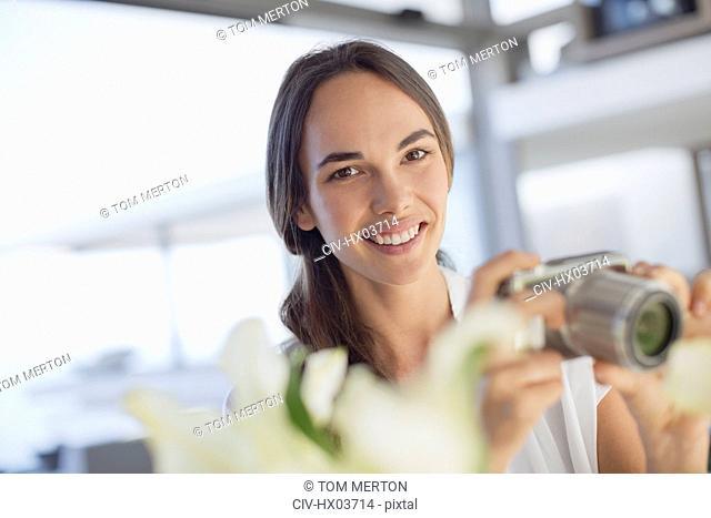 Portrait smiling brunette woman using digital camera