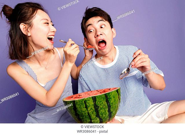 Fashionable young men and women eat watermelon