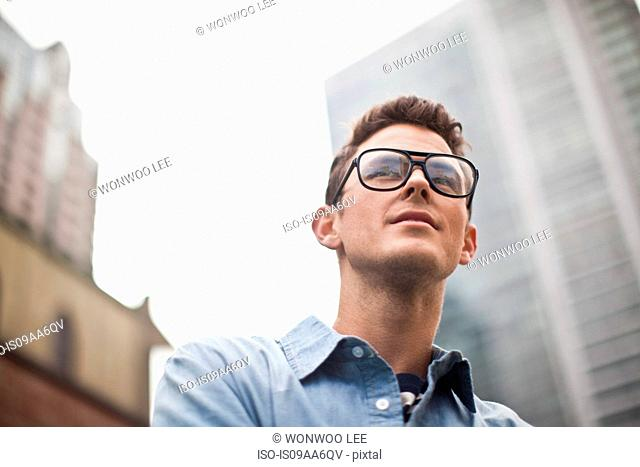 Young man in spectacles looking away, low angle view