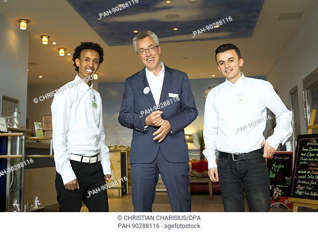 Hotel director Gabor Hnizdo (c) poses with the two refugees from Albania (r) and Eritrea at the restaurant of the town hotel in Rantum on the North Sea island...