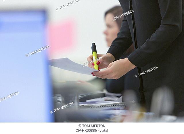Businesswoman highlighting paperwork in office
