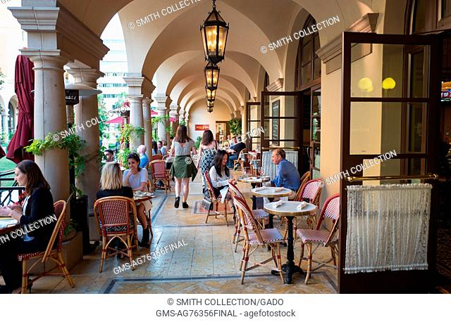 On the outdoor patio of Bar Bouchon, part of the Bouchon bistro-style restaurant owned by chef Thomas Keller, diners talk and enjoy their meals, Beverly Hills