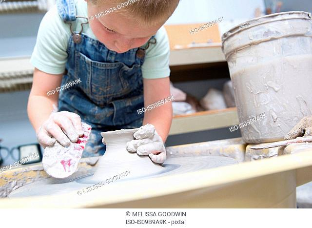 Boy shaping clay on potter's wheel