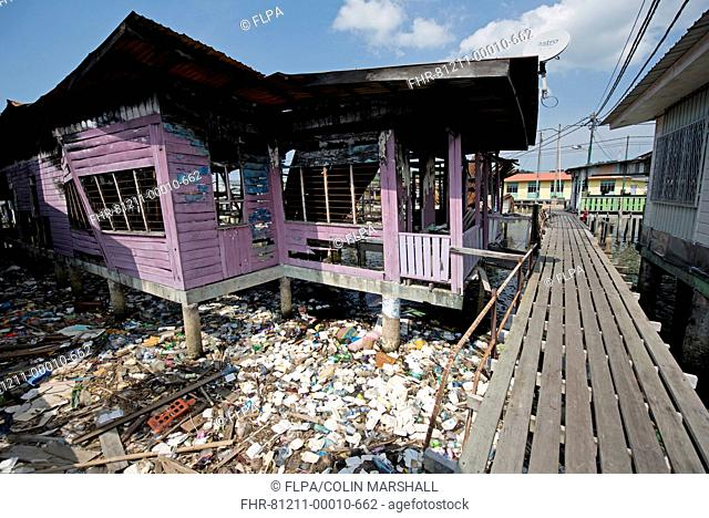 Walkway and burnt-out shack on stilts with washed up rubbish from river, Water Village (Kampong Ayer), Brunei River, Bandar Seri Begawan, Brunei, March