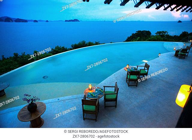 Six Senses Resort, Koh Yao Noi, Phang Nga Bay, Thailand, Asia. Romantic table in the restaurant near the swimming pool called The Hilltop Reserve in front of...