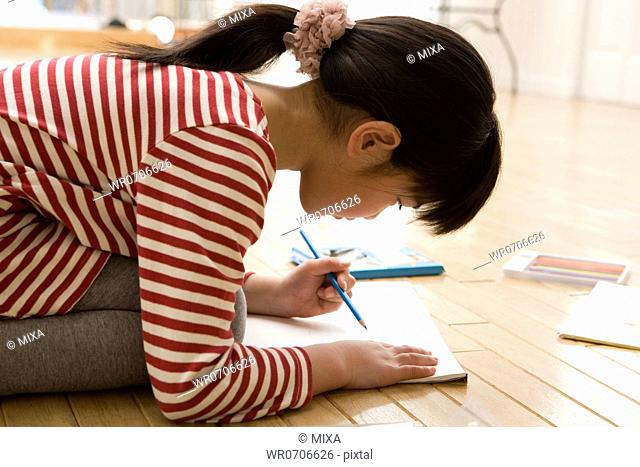 Girl kneeling and drawing picture