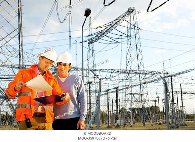 Male architects reviewing documents together at electric power plant