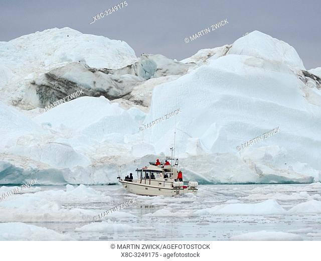 Exkursion boat with tourists. Ilulissat Icefjord also called kangia or Ilulissat Kangerlua at Disko Bay. The icefjord is listed as UNESCO world heritage