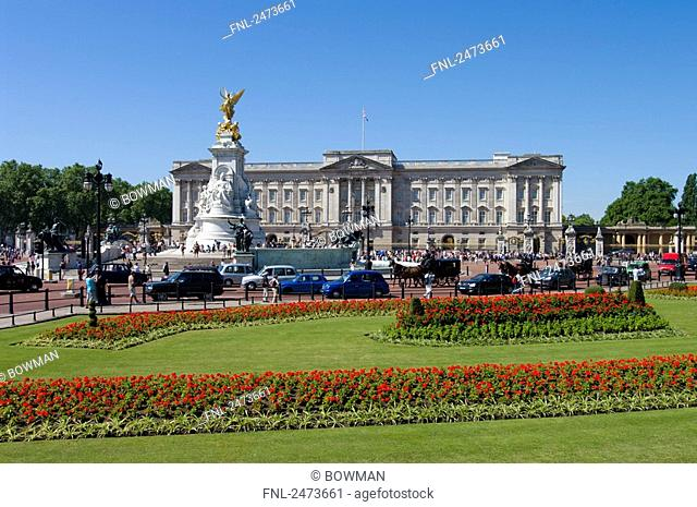 Flowers blooming in garden with palace in background, Buckingham Palace, City Of Westminster, London, England