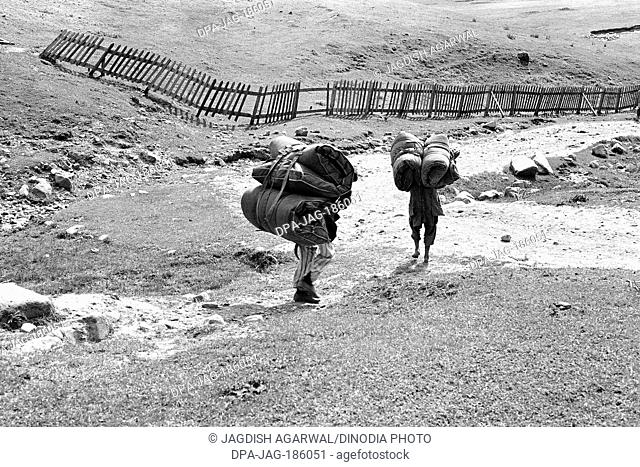 Two porters carrying heavy luggage Gulmarg Jammu and Kashmir India Asia 1971