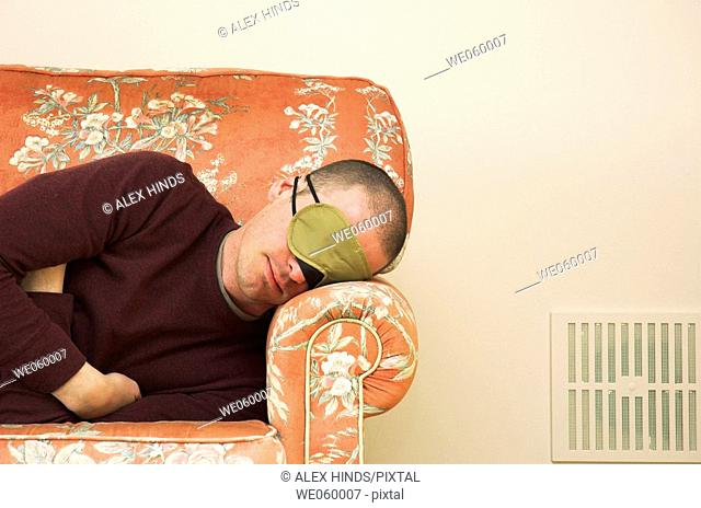 Young man wearing eye mask catching up on some sleep on a floral sofa
