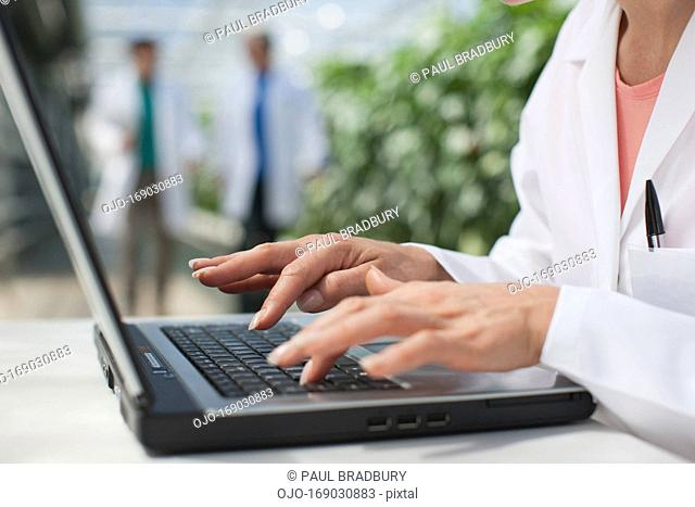 Scientist using computer in greenhouse