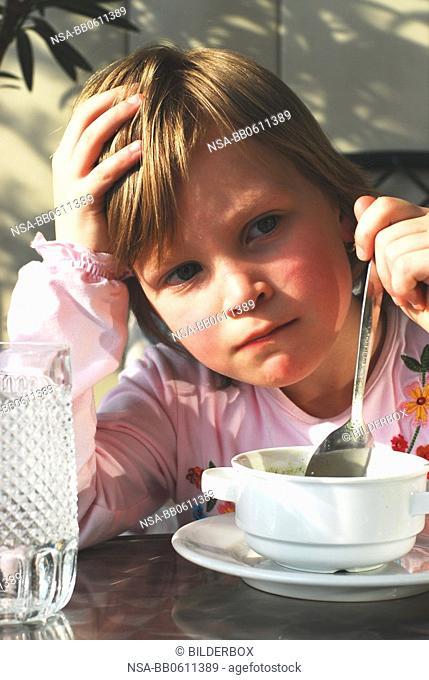 girls eats a soup