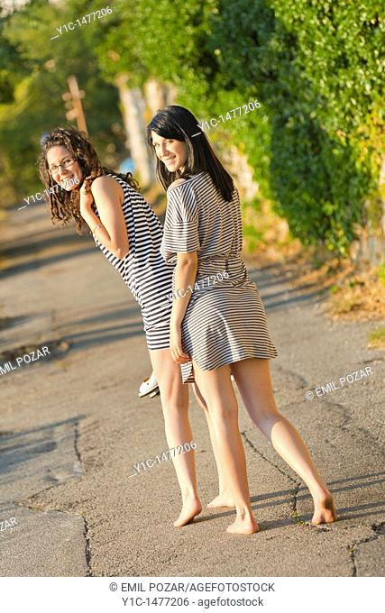Two attractive young women are walking barefeet