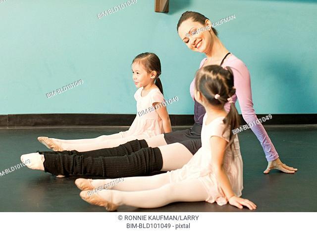 Girls taking ballet lessons from teacher