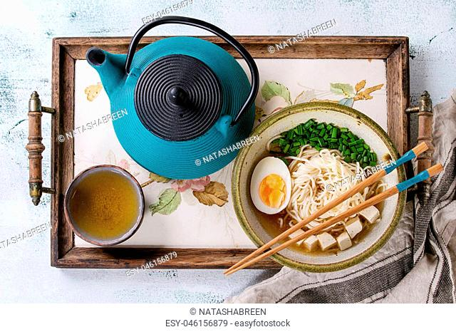 Bowl of asian style soup with noodles, egg, spring onion and tofu cheese, served with chopsticks, teapot and cup of green tea on wood tray with textile over...