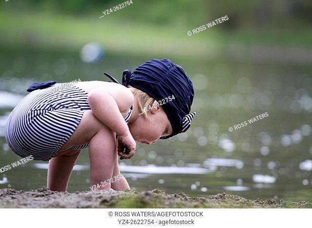 A female toddler in a swimming suit at Fish Lake, Spokane, Washington, USA