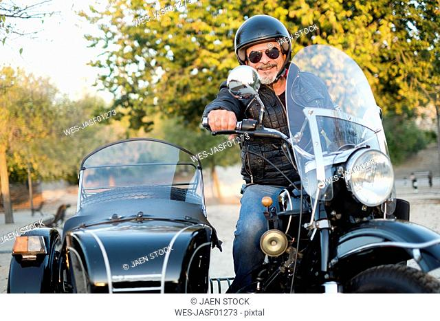 Portrait of smiling biker wearing helmet and sunglasses on his sidecar motorcycle