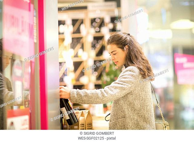 Young woman choosing bottle of red wine in supermarket