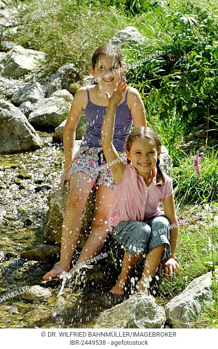 Girls playing and splashing with water, water fight, Kräuter-Erlebnis-Park herb theme park, Bad Heilbrunn, Loisachtal, Tölzer Land, Upper Bavaria, Germany