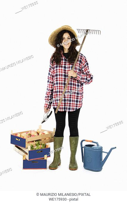 Young farmer with shears in hand and rake on his shoulder, at his feet crates with fruit and vegetables, she wears a straw hat